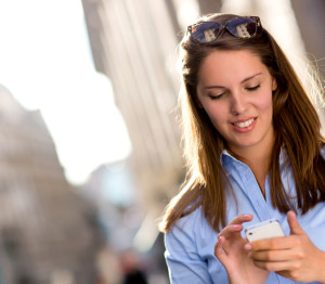 Woman texting on her mobile phone looking happy